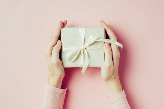 Las manos de la mujer que sostienen la caja de regalo en el fondo rosado, visión superior