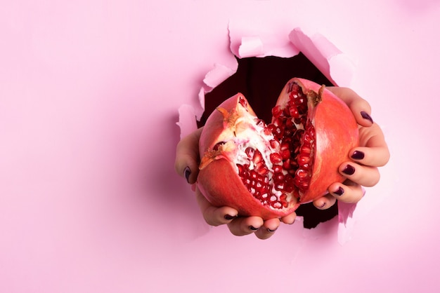 Las manos de la mujer que sostienen la granada madura dan fruto a través de fondo de papel rosado rasgado. jugo de fruta fresca.