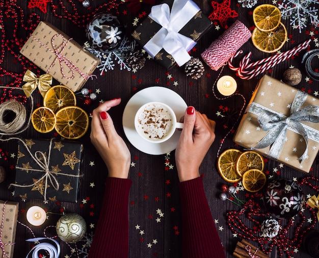 Las manos de la mujer que sostienen la taza de café beben la caja de regalo de vacaciones de la navidad en la tabla festiva adornada