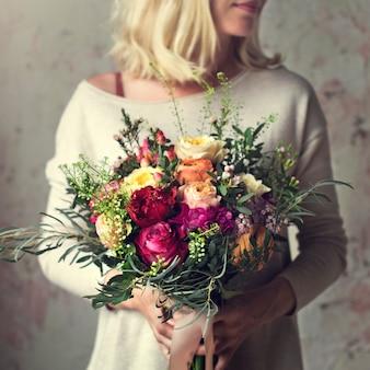 Manos de mujer con ramo de flores hermosas