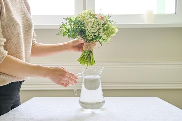 Manos de mujer con ramo de flores en un jarrón sobre la mesa