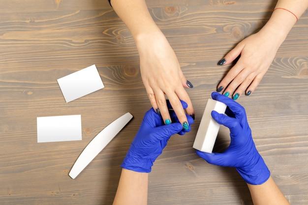 Manos de mujer recibiendo una manicura en salón de belleza