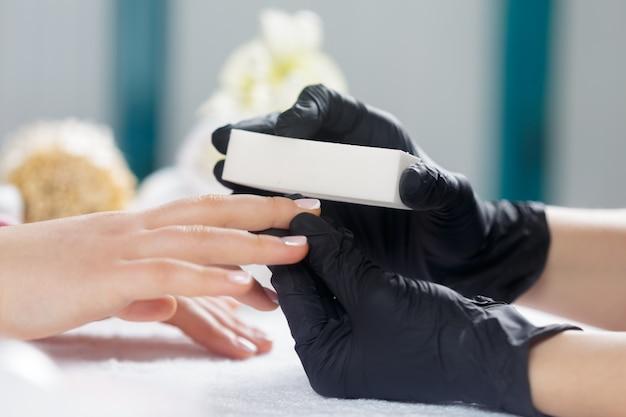 Manos de mujer recibiendo una manicura en un salón de belleza