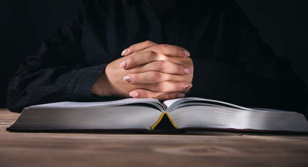 Manos de mujer rezando con una biblia en una habitación oscura