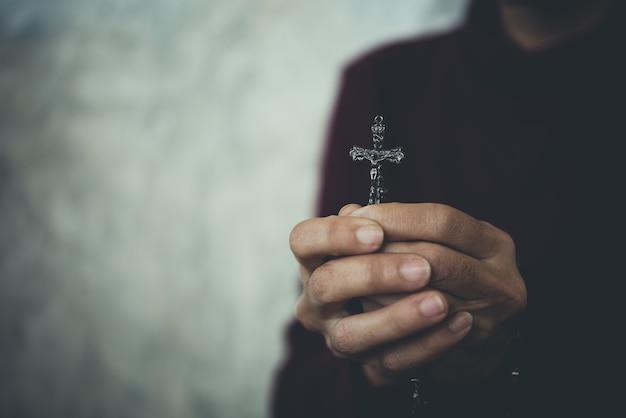 Manos de mujer rezando, cruzan en concepto religioso.