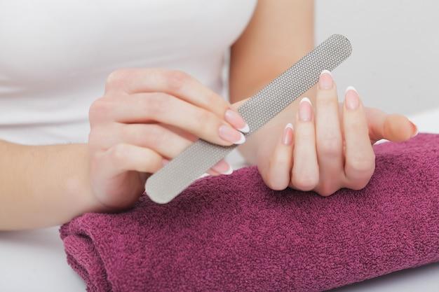 Manos de mujer en un salón de manicura recibiendo un procedimiento de manicura. manicura spa.