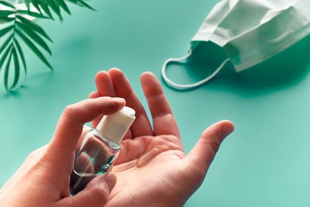 Manos de mujer senior con desinfectante, jabón de manos. hojas de fondo verde menta con mascarilla y palmera. buena higiene, medidas profilácticas para combatir el nuevo coronavirus.