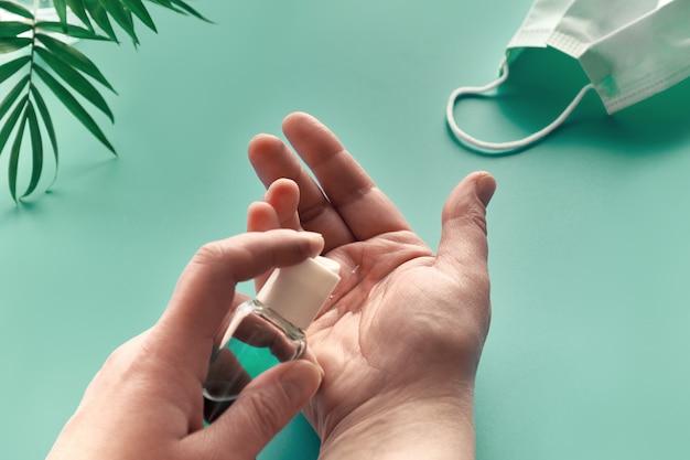 Manos de mujer senior con desinfectante, jabón de manos. pared verde menta con mascarilla y hoja de palmera. aislamiento social, higiene, medidas profilácticas para combatir el nuevo coronavirus que causa covid-19.