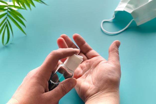 Manos de mujer senior con desinfectante, jabón de manos. pared verde menta con mascarilla, pastillas, hoja de palmera natural. aislamiento social, higiene, medidas profilácticas para combatir nuevos coronavirus.