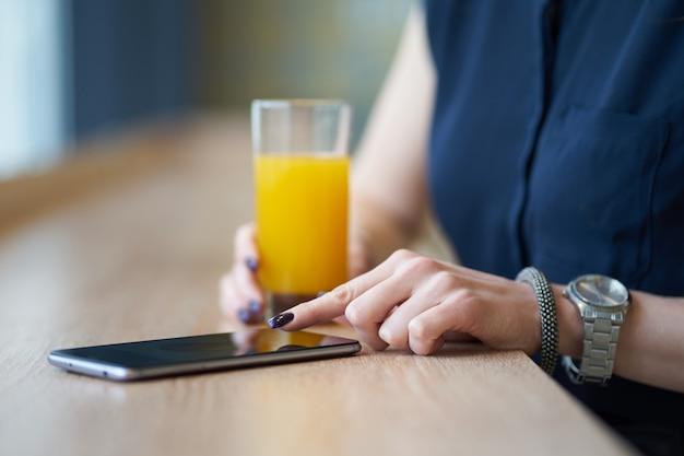Manos de mujer, con smartphone en café