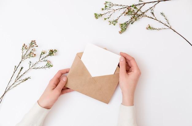 Manos de mujer con sobre de kraft con tarjeta de invitación de boda en blanco