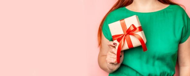 Manos de mujer sosteniendo la actual caja con lazo rojo sobre fondo rosa pastel.