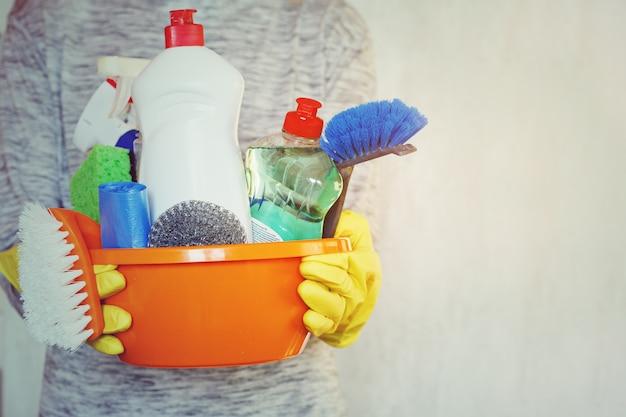 Manos de mujer sosteniendo la bañera con productos de limpieza.