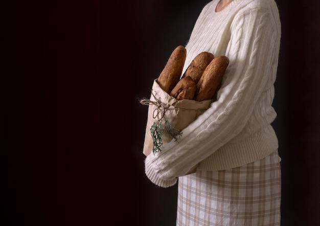 Manos de mujer sosteniendo la bolsa de compras con pan para vacaciones