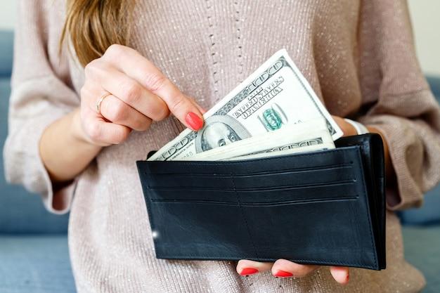 Manos de mujer sosteniendo bolso con dinero en efectivo