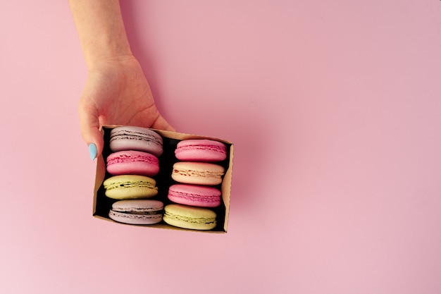 Manos de mujer sosteniendo la caja con coloridas galletas de macarrón, espacio de copia