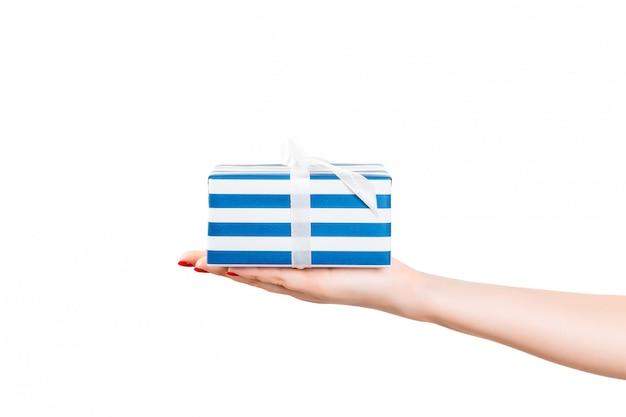 Manos de mujer sosteniendo una caja de regalo envuelta