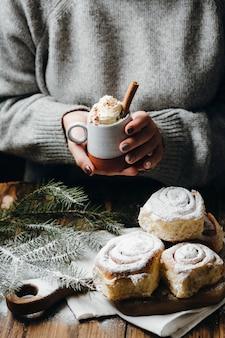 Manos de mujer sosteniendo chocolate caliente con crema batida y canela