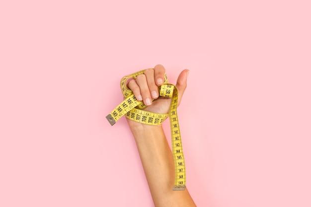 Manos de mujer sosteniendo una cinta métrica sobre un fondo rosa