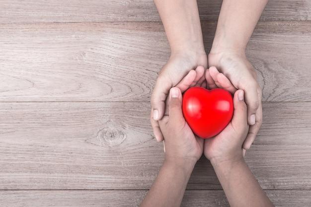 Manos de mujer sosteniendo corazón rojo y estetoscopio