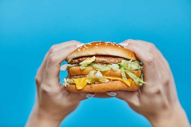 Manos de mujer sosteniendo una hamburguesa en un azul