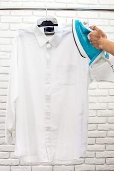 Manos de mujer sosteniendo hierro caliente, ropa humeante
