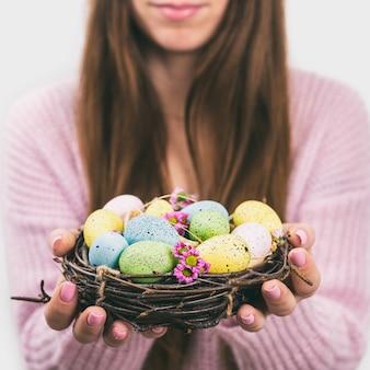 Manos de mujer sosteniendo huevo de pascua pintado en un pequeño nido