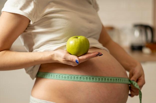 Manos de mujer sosteniendo una manzana y midiendo su vientre