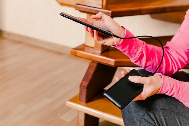 Manos de mujer sosteniendo negro smartphone cargando batería del banco de energía externo