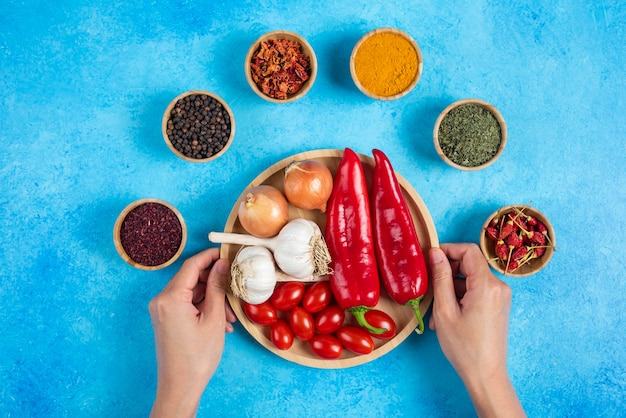 Manos de mujer sosteniendo plato de verduras.