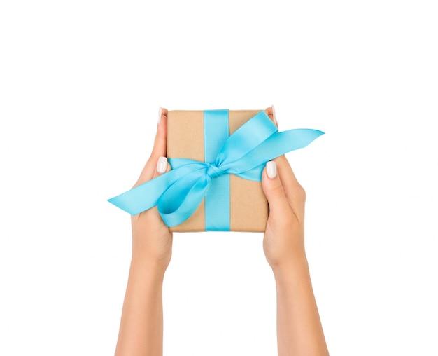 Manos de mujer sosteniendo regalo envuelto y decorado con lazo azul aislado en blanco