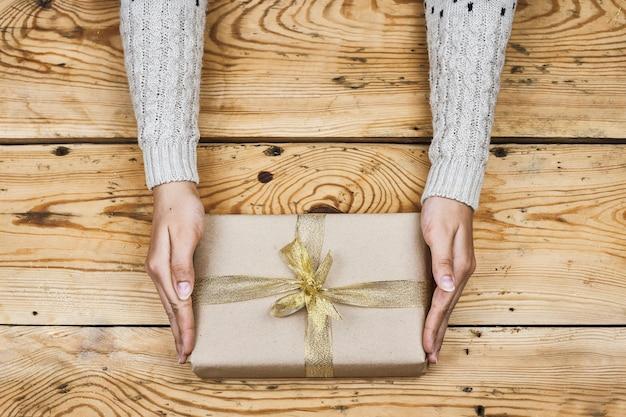 Manos de mujer sosteniendo regalo de navidad inclinado con una cinta dorada