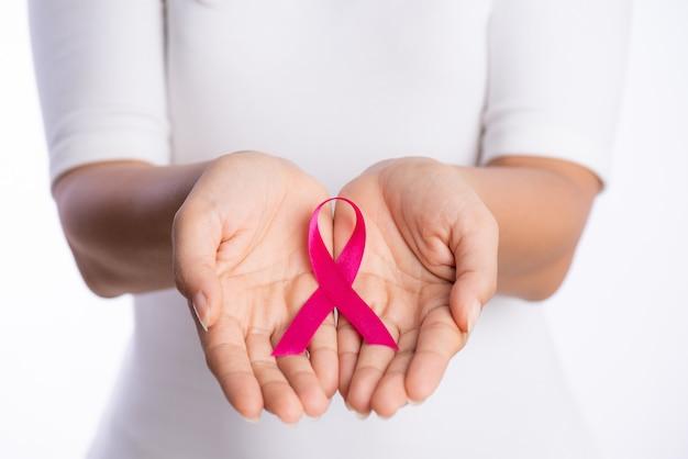 Manos de mujer sosteniendo rosa cinta de conciencia de cáncer de mama en blanco