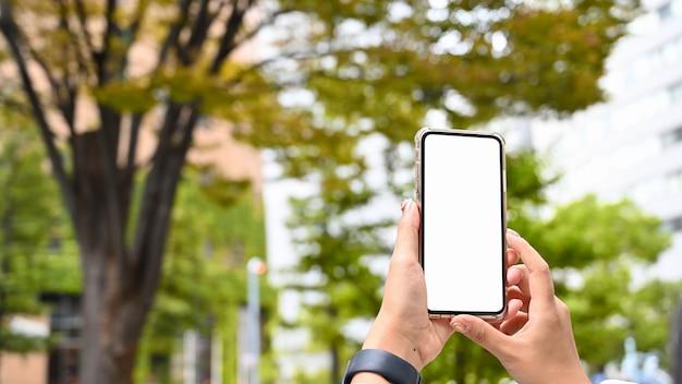 Manos de mujer sosteniendo smartphone en parque con otoño.