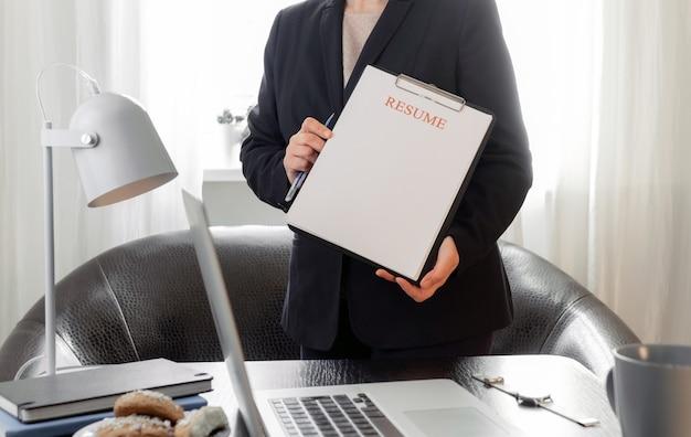 Manos de mujer sosteniendo la solicitud de currículum cerca de su lugar de trabajo con computadora portátil.