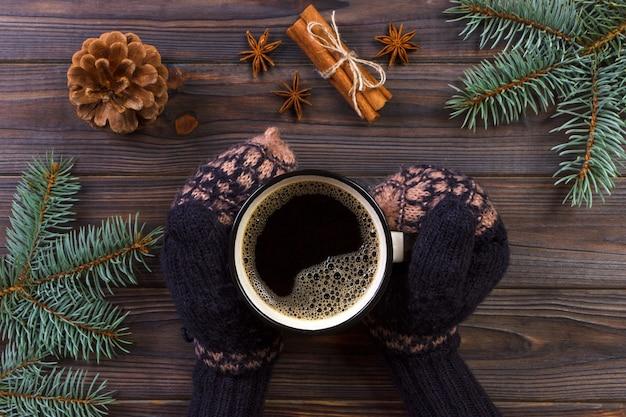 Manos de mujer sosteniendo la taza de café. decoraciones navideñas, fondo de navidad