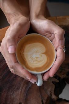 Manos de mujer sosteniendo una taza de café en la mesa de madera