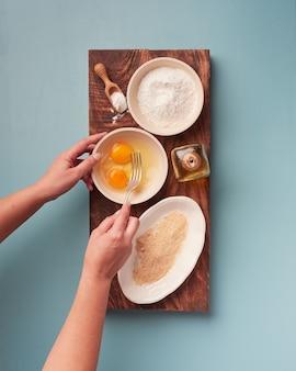 Manos de mujer sosteniendo un tenedor para batir huevos con varios ingredientes de cocina en una tabla de madera colocada sobre una tabla de madera oscura rectangular