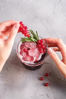 Manos de mujer sostiene bayas de grosella para la preparación de cóctel de frutas frescas heladas en vidrio con hoja de romero, mesa de piedra de hormigón, vista de ángulo