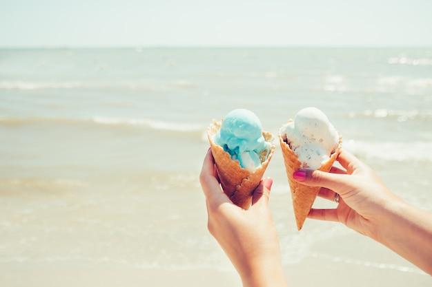 Las manos de la mujer sostiene dos helados en el mar