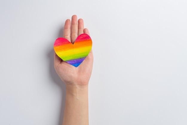 Las manos de la mujer sostienen la conciencia del corazón del arco iris para el concepto de orgullo de la comunidad lgbt
