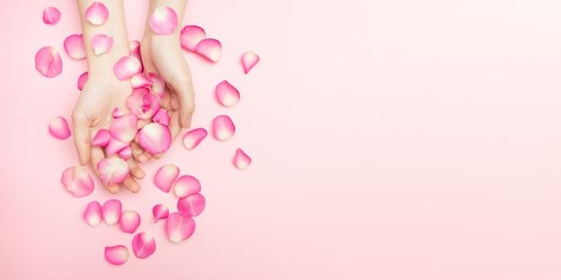 Las manos de la mujer sostienen las flores color de rosa en un fondo rosado. una muñeca delgada y manicura natural. cosméticos para el cuidado de la piel sensible. cosmética natural de pétalos, cuidado de manos antiarrugas.