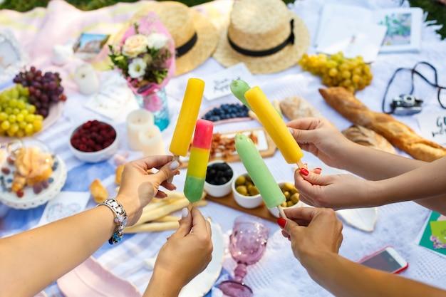 Las manos de la mujer sostienen los palillos coloridos del helado en la comida campestre del verano. fines de semana de verano
