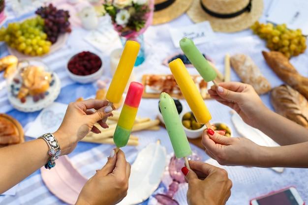 Las manos de la mujer sostienen los palillos coloridos del helado en el fondo de la comida campestre del verano. fines de semana de verano