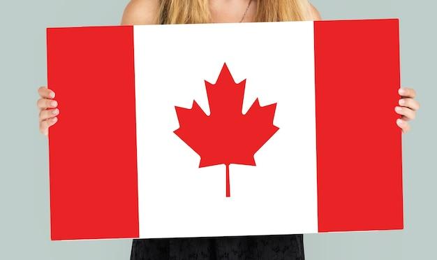 Manos de mujer sostienen el patriotismo de la bandera de canadá