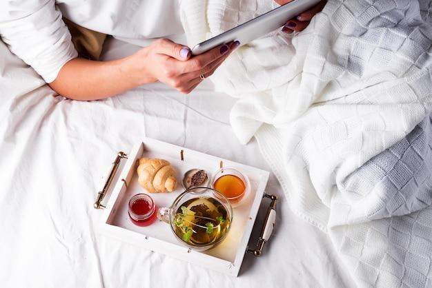 Las manos de la mujer sostienen la tableta. una mañana acogedora en la cama con croissants, mermelada y té.