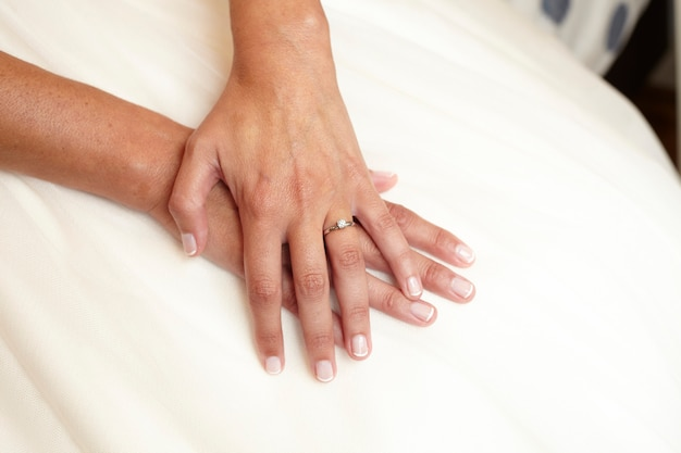 Manos de mujer en su vestido de novia