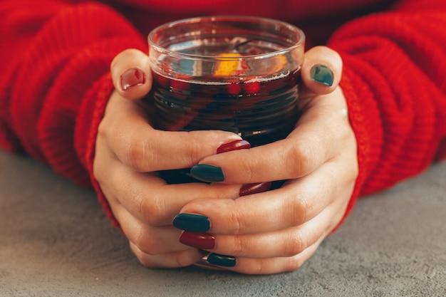 Manos de mujer en suéter caliente sosteniendo una copa de vino caliente
