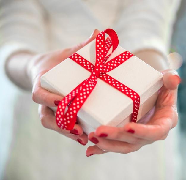 Manos de mujer sujetando una caja de regalo