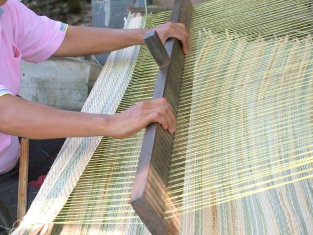 Manos de mujer tailandesa tejiendo estera de caña